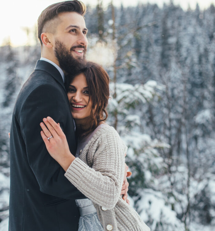Bearded man and his lovely bride pose on the snow in a magic win